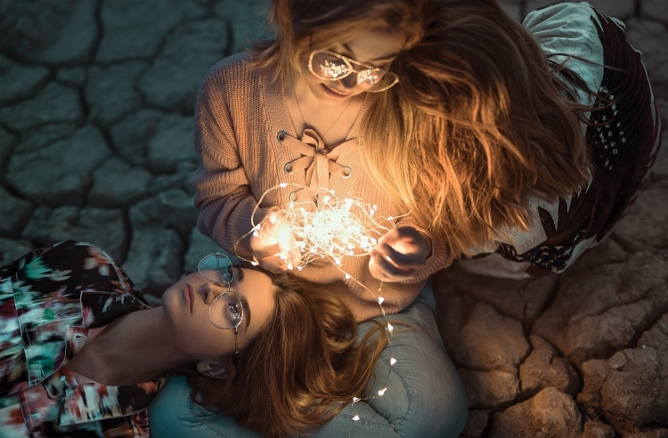 Two girls with a string of lights